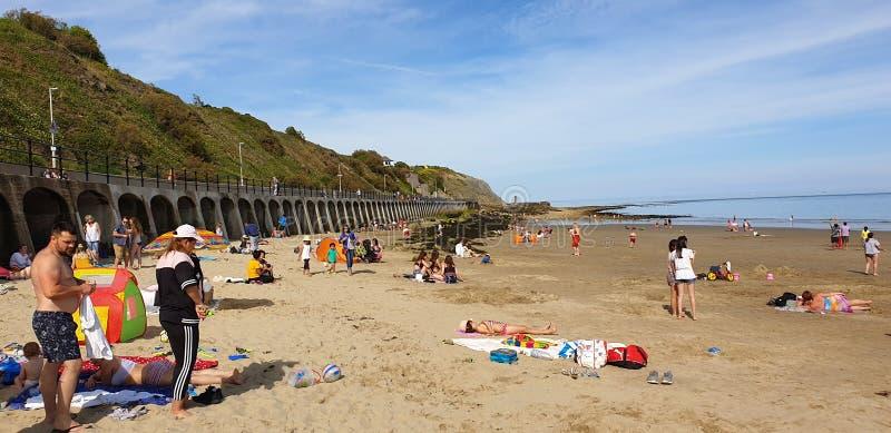 Londen, Engeland, Folkestone, Kent: 1 juni 2019: Toeristen die op Zonnig zandstrand van de mooie zonneschijn en van de blauwe hem stock foto
