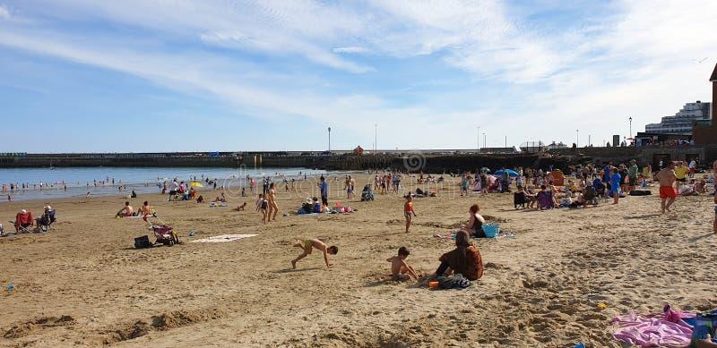 Londen, Engeland, Folkestone, Kent: 1 juni 2019: Toeristen die op Zonnig zandstrand van de mooie zonneschijn en van de blauwe hem royalty-vrije stock afbeeldingen