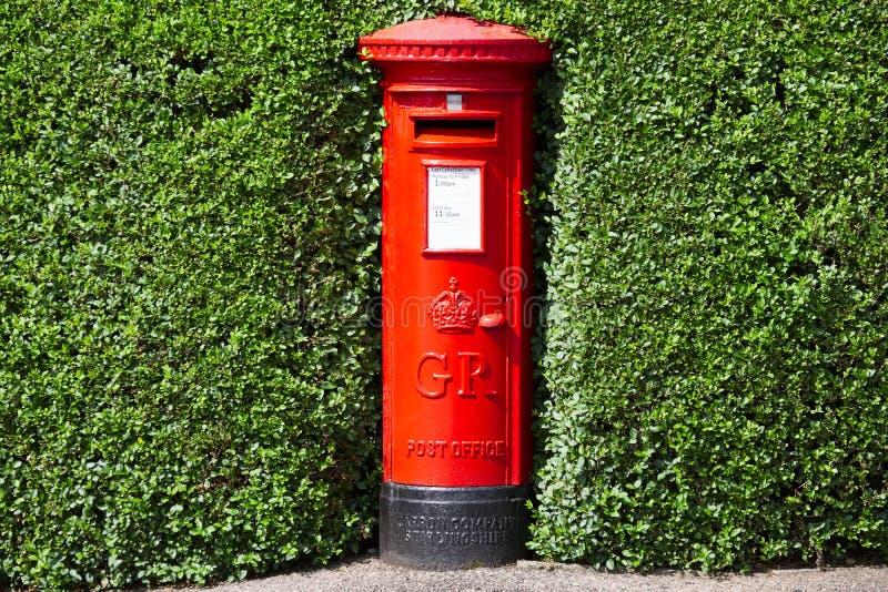 Londen, Engeland/het UK - 13 Juli 2019: Rode die de pijlerpostbox van Royal Mail in groene haagstruik wordt verborgen royalty-vrije stock fotografie