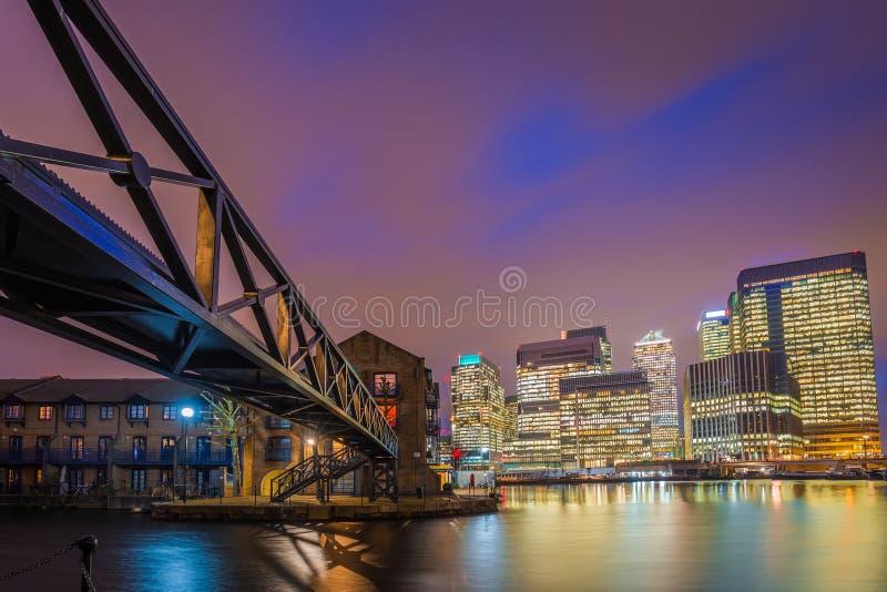 Londen, Engeland - Kleurrijke nachthemel bij het financiële district van Canary Wharf met skyscapers stock afbeelding