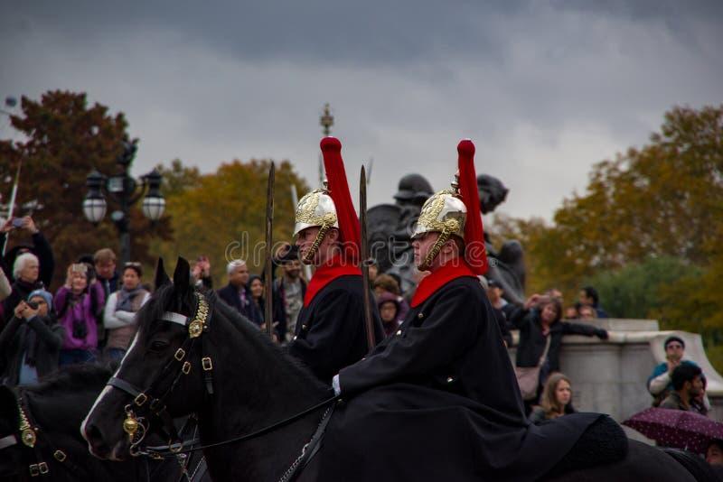 LONDEN, ENGELAND - 9 NOV. 2018: Twee militairen in traditionele eenvormige het berijden paarden De ceremonie van het Buckinghampa stock foto