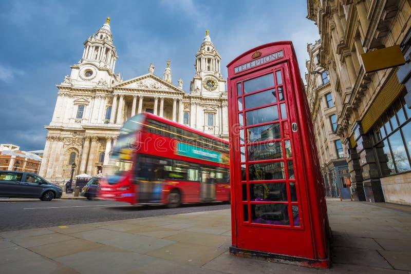 Londen, Engeland - Traditionele rode telefooncel met iconische rode dubbeldekkerbus in beweging bij de Kathedraal van StPaul ` s stock afbeeldingen