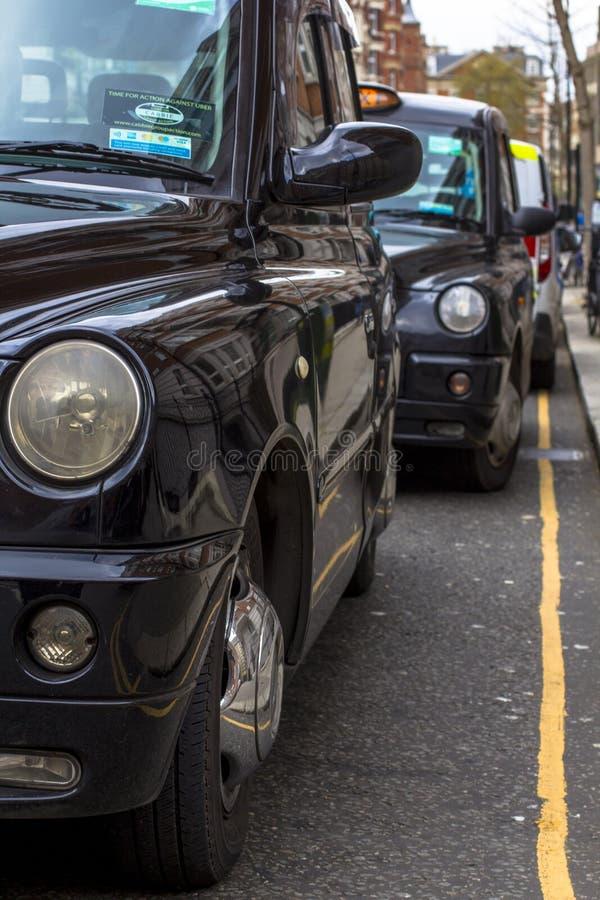 Londen, Groot-Brittanni? 12 april, 2019 Kensingtonstraat Cabineparkeren De cabine van Londen wordt beschouwd als de beste taxi in stock foto