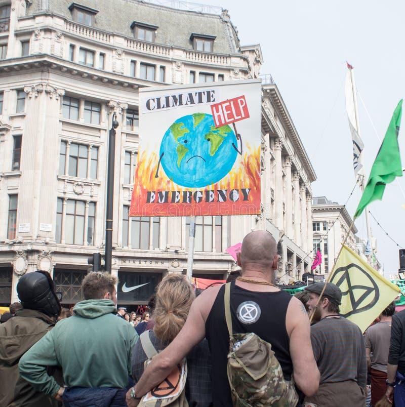 Londen, het UK, 17 April 2019 - de Protesteerders houden een banner en een vlag bij een klimaatveranderingprotest buiten ondergro stock foto's