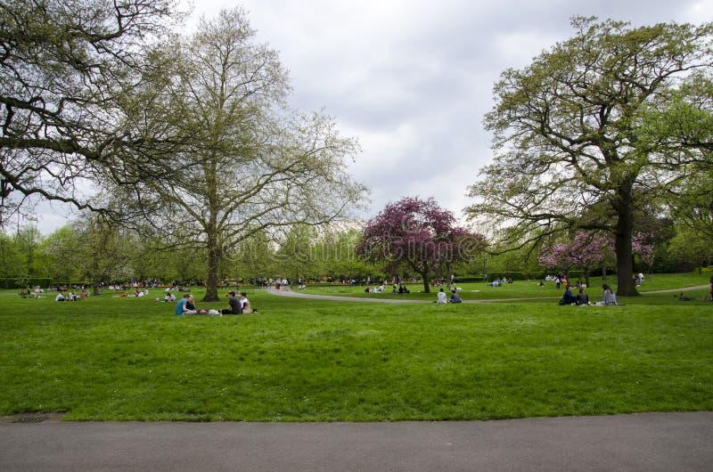 Londen, het UK 22 April 2018 Mensen die rust in een bewolkt pari krijgen royalty-vrije stock foto's