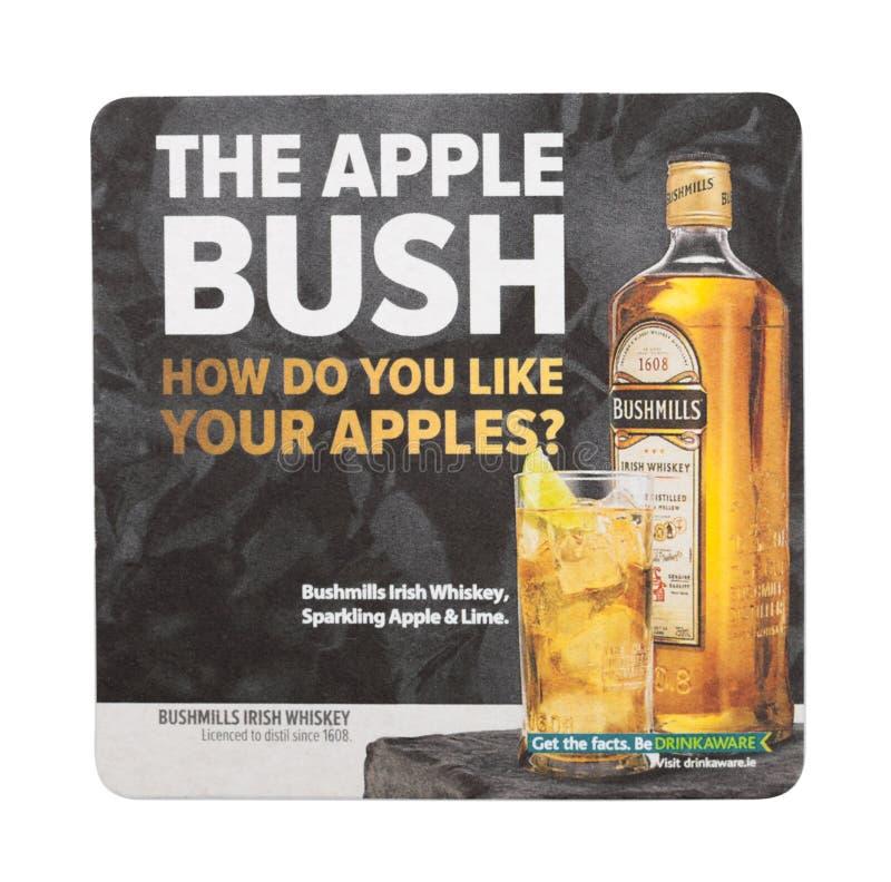 LONDEN, HET UK - 22 AUGUSTUS, 2018: De matonderlegger voor glazen van de Bushmills Ierse die whisky op witte achtergrond wordt ge stock foto's