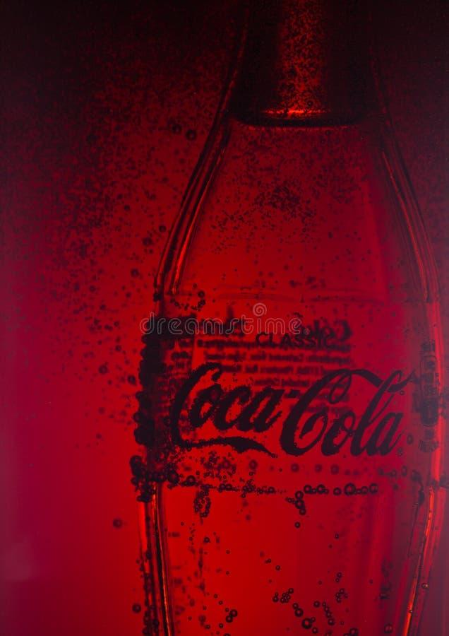LONDEN, HET UK - 02 JANUARI, 2018: Koud glasfles van Coca Cola-drank binnen de container van het kolaglas De drank wordt geproduc stock foto