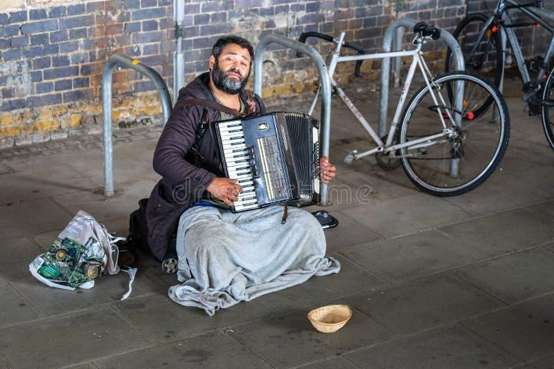 Londen, het UK, Juli, 2019 Dakloze Mens het Spelen Harmonika stock afbeelding