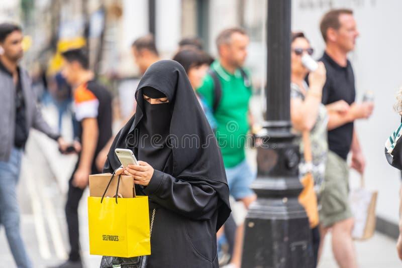Londen, het UK, Juli, 2019 Een Moslimvrouw in Londen die een niqab dragen, die mobiele telefoon met behulp van terwijl het winkel stock foto
