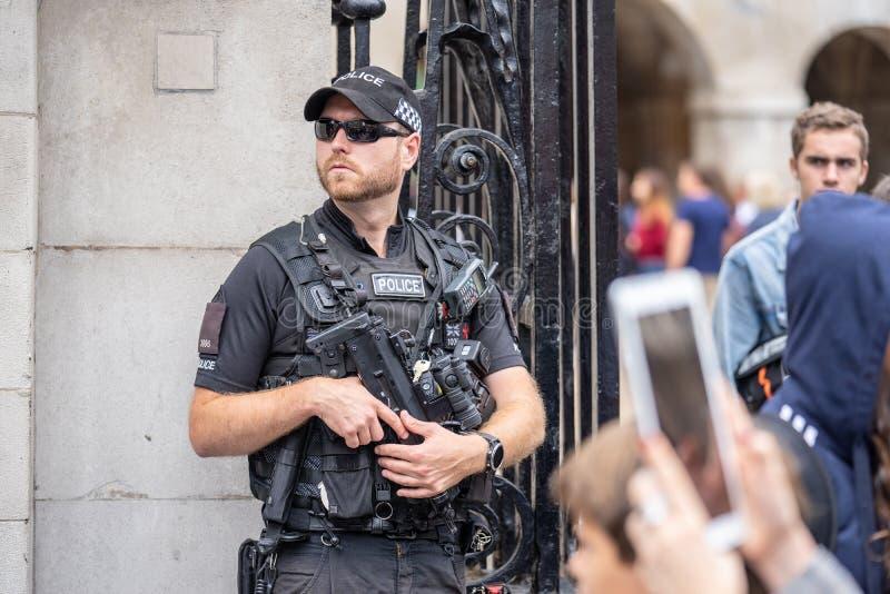 Londen, het UK, Juli, 2019 Een politieman met een machinegeweer die steek dragen en het kogelbewijs bekleden royalty-vrije stock afbeeldingen