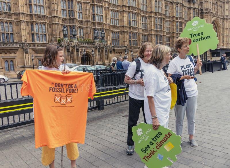 Londen/het UK - 26 Juni 2019 - Activisten die tekens over klimaatverandering en fossiele brandstoffen houden royalty-vrije stock foto