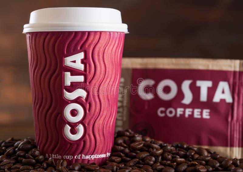 LONDEN, HET UK - 05 JUNI, 2019: Costa Coffee Paper Cup met pak van Origineel Costa Coffee met bonen op houten achtergrond stock afbeeldingen