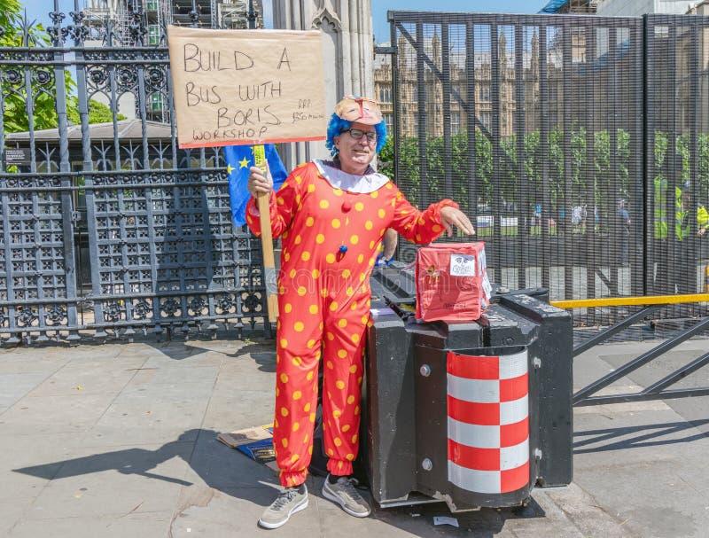 Londen/het UK - 26 Juni 2019 - protesteerder de pro-EU anti-Brexit kleedde zich aangezien een clown en het houden 'een bus met he royalty-vrije stock foto's