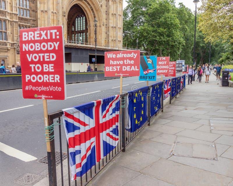 Londen/het UK - 26 Juni 2019 - tekens de pro-EU anti-Brexit en Europese Unie/Union Jack-vlaggen buiten het Parlement stock afbeelding