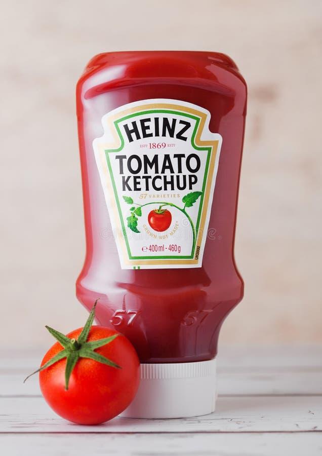 LONDEN, HET UK - 10 MAART, 2018: Plastic fles van Heinz Ketchup op hout met ruwe tomaat Vervaardigd door H J Heinz Company stock afbeeldingen