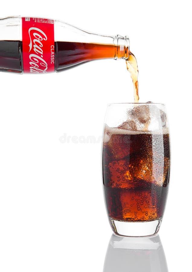 LONDEN, HET UK - 07 NOVEMBER, 2016: Klassieke fles Coca-Cola-het gieten in glas op witte achtergrond stock foto