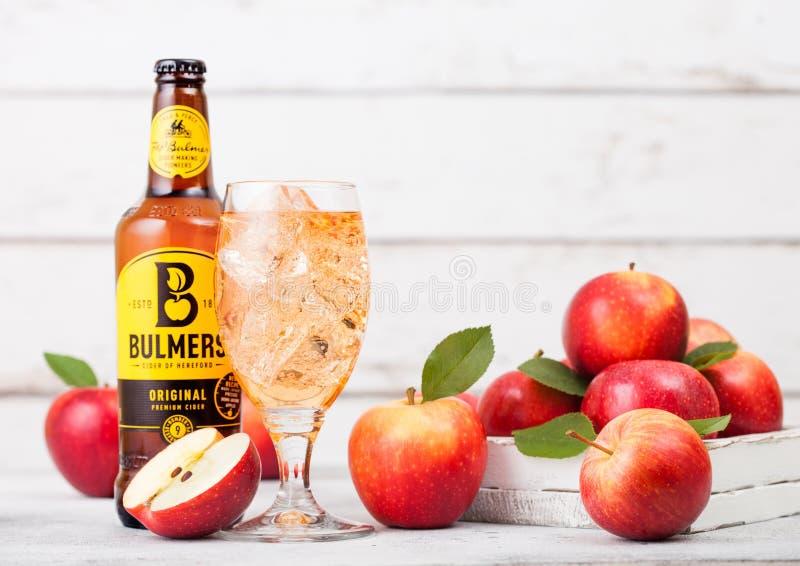 LONDEN, HET UK - 13 SEPTEMBER, 2018: Fles de Originele Cider van Bulmers en glas van ijsblokjes met verse appelen op houten achte stock afbeeldingen
