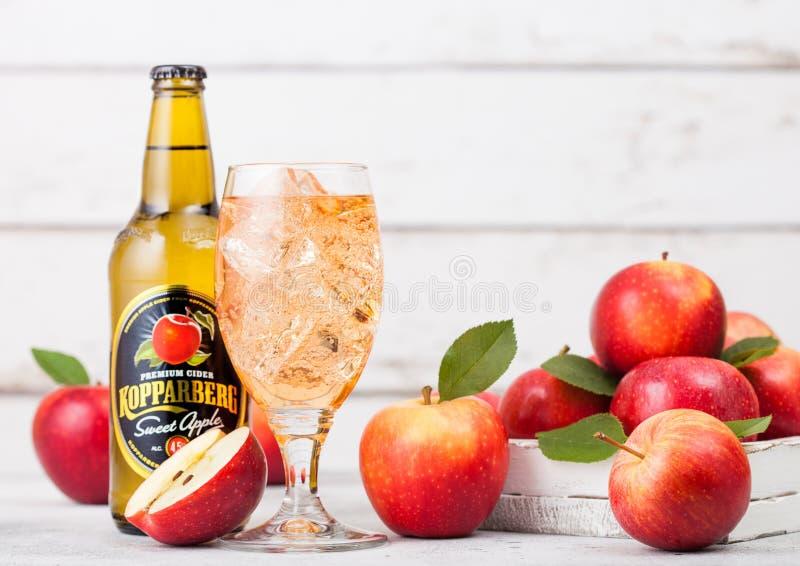 LONDEN, HET UK - 13 SEPTEMBER, 2018: Fles en glas Zoete de appelcider van Kopparberg met verse appelen op houten achtergrond royalty-vrije stock afbeeldingen