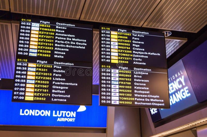 LONDEN, het VERENIGD KONINKRIJK - April 12, 2015: Het de raadsscherm van het luchthavenvertrek bij de luchthaven van Luton in Lon royalty-vrije stock afbeelding