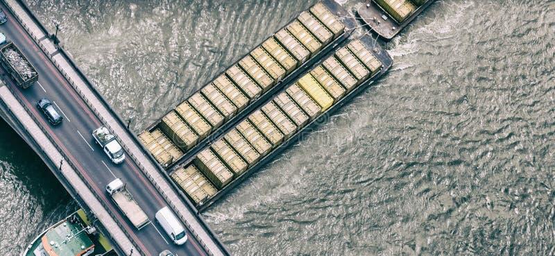 LONDEN - JUNI 2015: De rivier van Theems van vrachtschipkruisen De haven van royalty-vrije stock afbeelding
