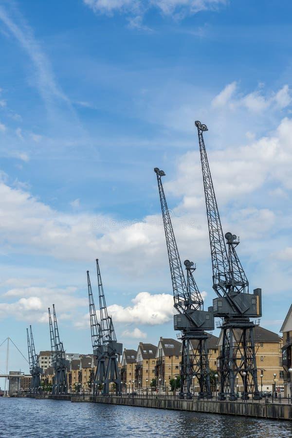 LONDEN - JUNI 25: Oude havenkranen naast een waterkant DE stock afbeeldingen