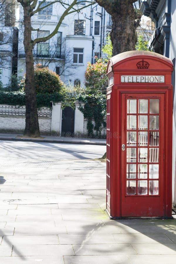 Londen - Maart 30: Iconische rode telefooncel voor witte rijtjeshuizen in Kensington op 30 Maart, 2017 stock afbeeldingen