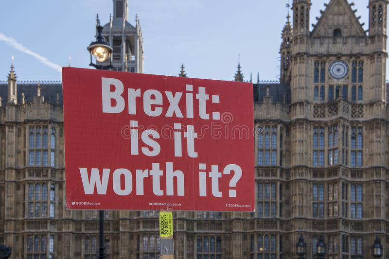 Red protest sign with text Brexit is it worth it in the front of the houses of stock photography