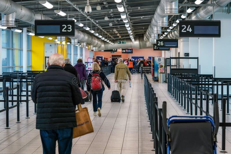 Londen, Verenigd Koninkrijk - februari 2019: Reizigers die in de vertrekhal lopen om naar de gate-desk te gaan voor hun vlucht, i royalty-vrije stock foto