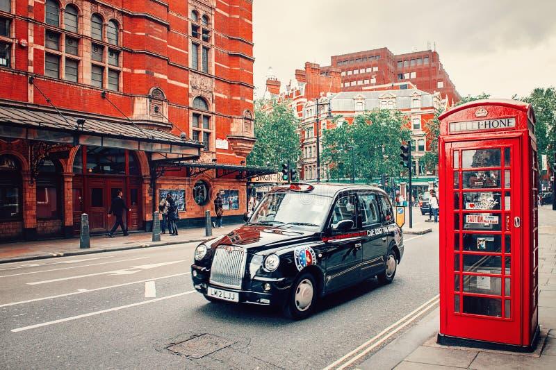 Londen Zwarte taxi en Rode Telefooncel op de straat met rode baksteengebouwen stock fotografie