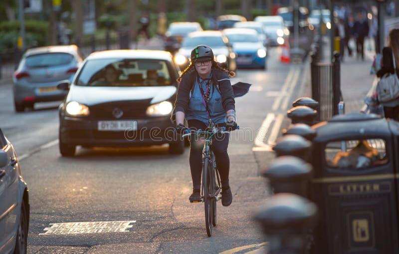 Londinenses que conmutan de trabajo en bici Opinión del camino con los coches y los motoristas fotografía de archivo