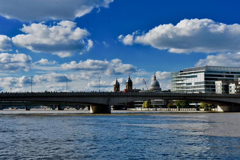 The river Thames and London Bridge. London Bridge stretching across the river thames in London under a silver lining clouds and blue sky royalty free stock images