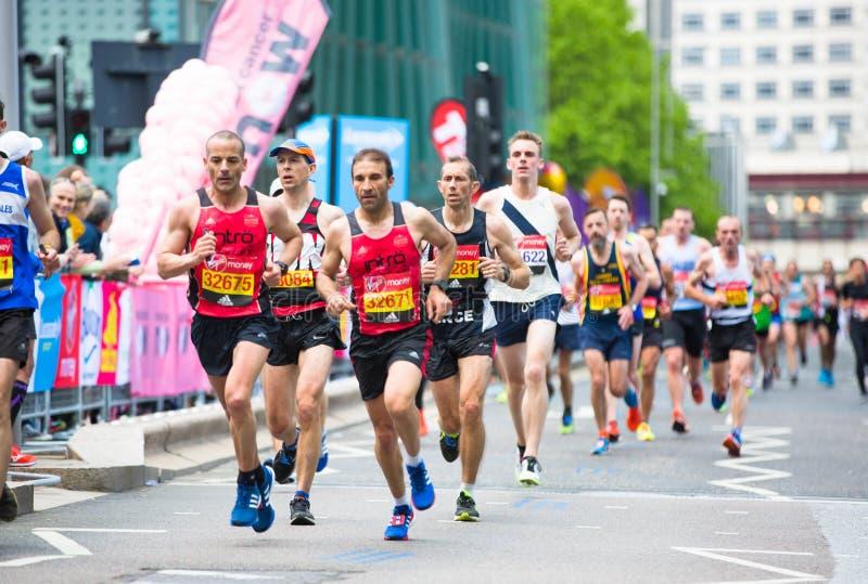 London, BRITISCHE Leute, die in London-Marathon laufen Leute, die den Sportlern in Canary Wharf-Bereich zujubeln stockbilder