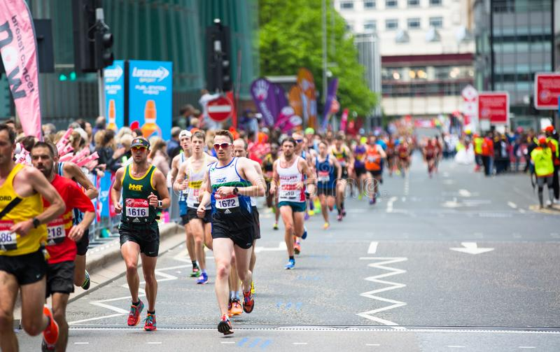 London, BRITISCHE Leute, die in London-Marathon laufen Leute, die den Sportlern in Canary Wharf-Bereich zujubeln stockbild