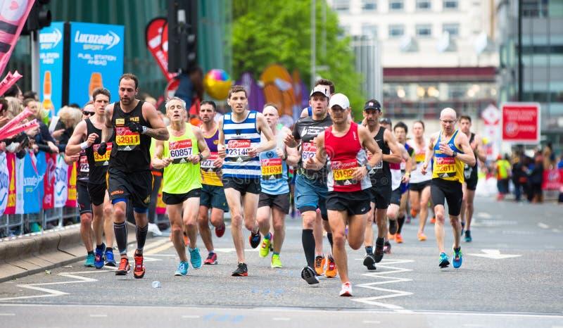 London, BRITISCHE Leute, die in London-Marathon laufen Leute, die den Sportlern in Canary Wharf-Bereich zujubeln stockfotos