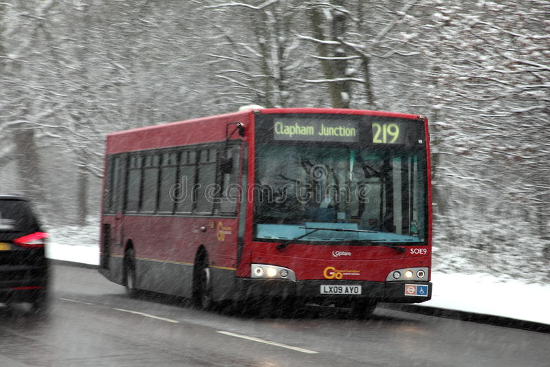 London-Bus in einem Schneeblizzard stockfotografie