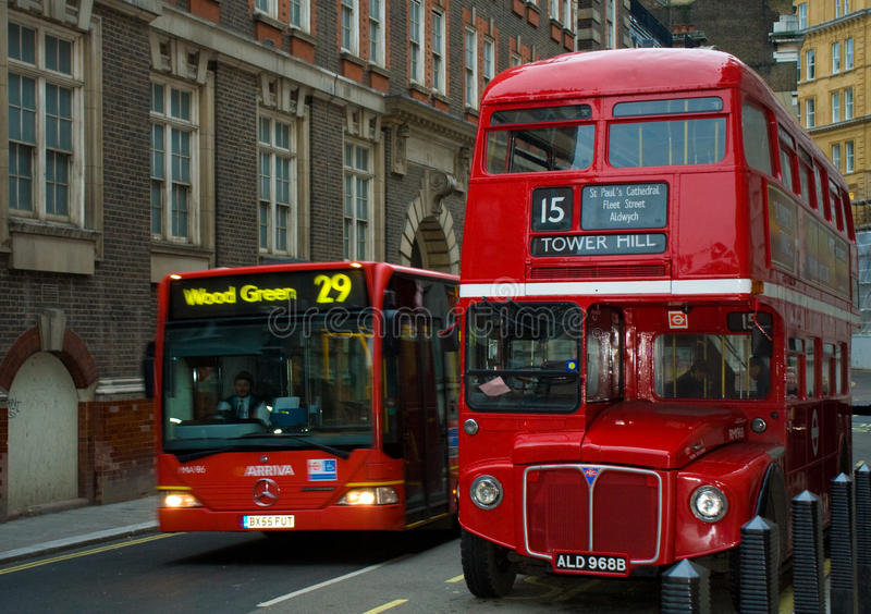 London Buses old and new. A 'bendy bus' overtakes a classic Routemaster in London royalty free stock image