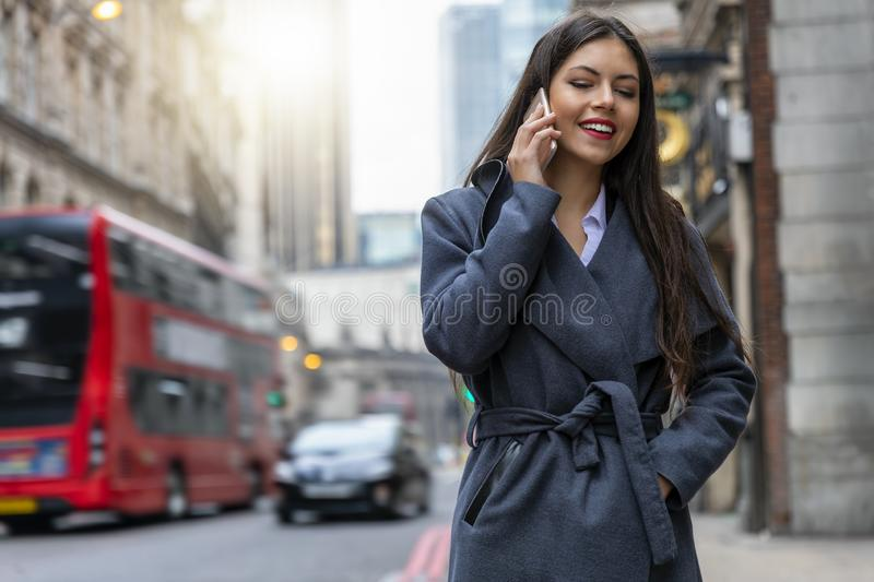 London businesswoman talking to her mobile phone. Attractive, confident London businesswoman walking down the street of the City talking to her mobile phone stock images