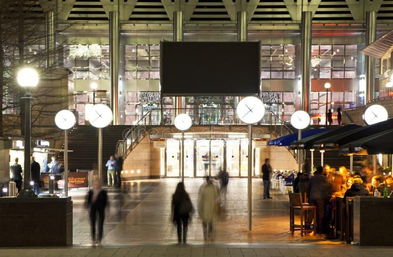 LONDON CANARY WHARF UK - APRIL 4, 2014 tänder den Canary Wharf fyrkantsikten i natt med kontorsarbetare som ut kyler arkivbilder