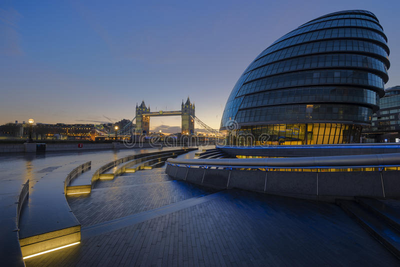 London City Hall. The view of the futuristic architecture of London City Hall with the historical landmark Tower Bridge in the background during dawn at London royalty free stock photos