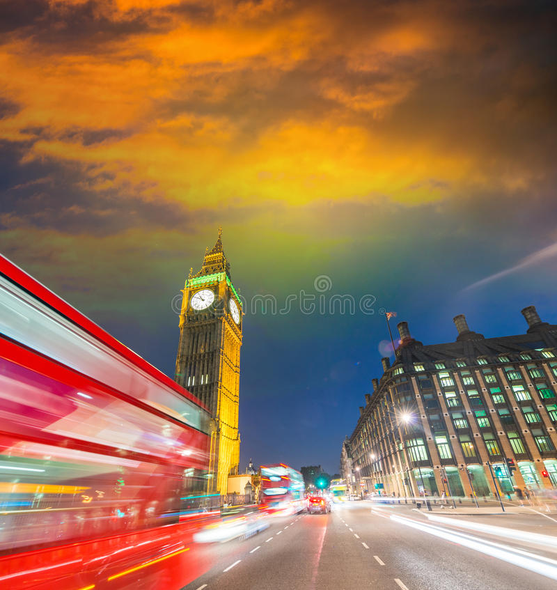 London. City night scene with red bus crossing Westminster. Traffic light trails royalty free stock image