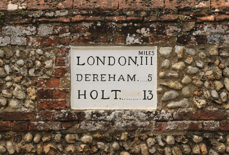 London 111, Dereham 5. Old mileage sign installed in a typical flint brick wall in North Elmham near Dereham stock images