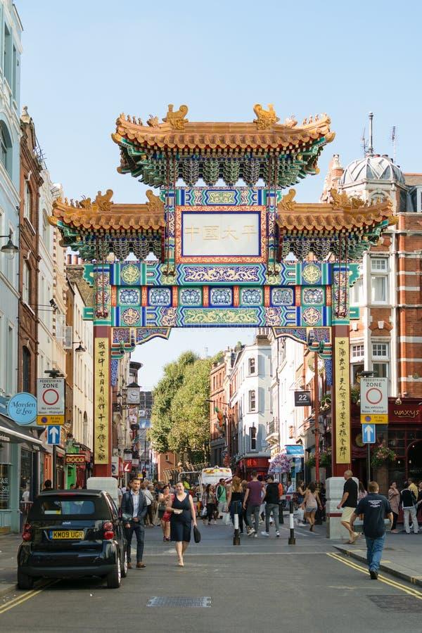 London, England - 30. August 2016: Leute überschreiten durch das neue chinesische Tor auf Wardour-Straße in Chinatown stockfotos