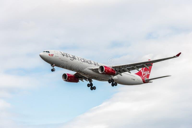 LONDON ENGLAND - AUGUSTI 22, 2016: Landning för flygbuss A330 för G-VGBR Virgin Atlantic Airways i den Heathrow flygplatsen, Lond arkivfoton