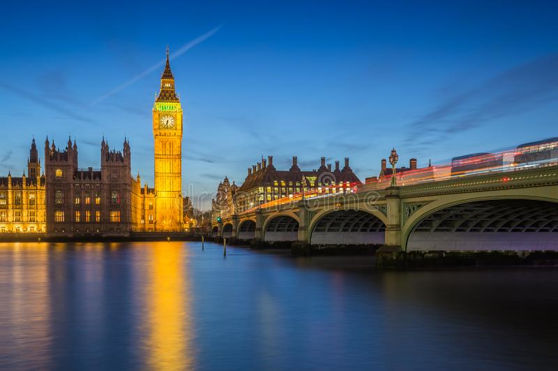 London, England - The Big Ben Clock Tower and Houses of Parliament with iconic red double-decker buses at city of westminster by royalty free stock photos