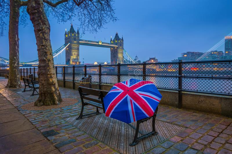London, England - British style umbrella on a bench with iconic illuminated Tower Bridge at background. At blue hour royalty free stock photo