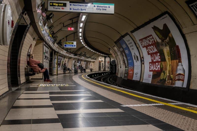 LONDON ENGLAND, DECEMBER 10, 2018: Folk som väntar på drevet på den Waterloo rörstationen som är full med tecken och annonseringa arkivfoton