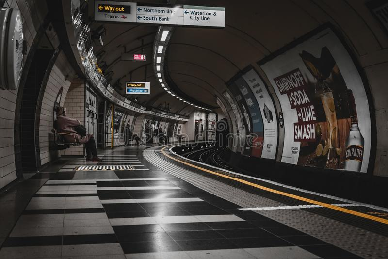 LONDON ENGLAND, DECEMBER 10, 2018: Folk som väntar på drevet på den Waterloo rörstationen som är full med tecken och annonseringa arkivfoto