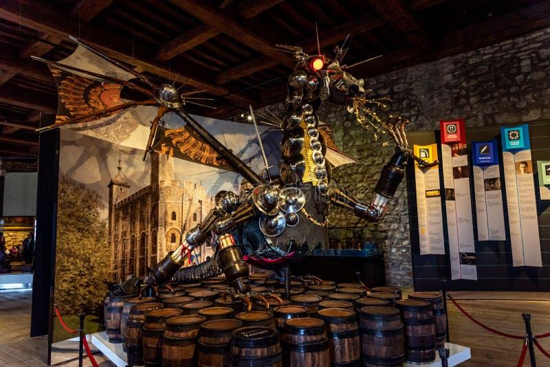 LONDON ENGLAND, DECEMBER 10th, 2018: betitlad vårdare för drake som staty installeras på ingången till utställningmakthuset, kron royaltyfri fotografi
