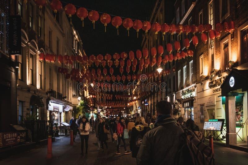 LONDON ENGLAND, DECEMBER 10th, 2018: Folk som går i den Kina staden som in dekoreras av kinesiska lyktor under jul och nytt år royaltyfria bilder