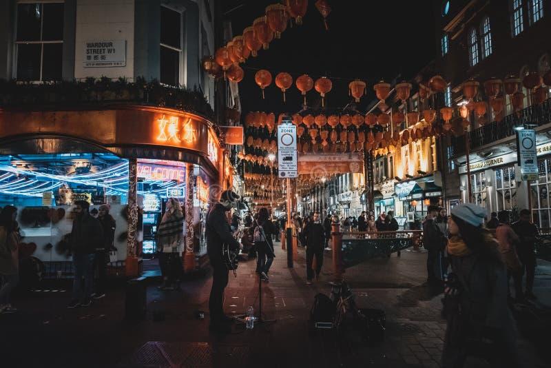 LONDON ENGLAND, DECEMBER 10th, 2018: gatamusiker som spelar gitarren under neonljus i kineskvarter Begrepp av likgiltighet och royaltyfria foton